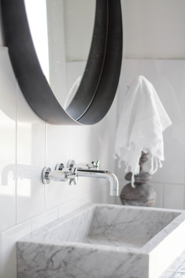 koa-house_pool-bathroom-black-and-white-block-marble-sink-white-tile-cb2-round-crescent-mirrow-wall-mount-faucet