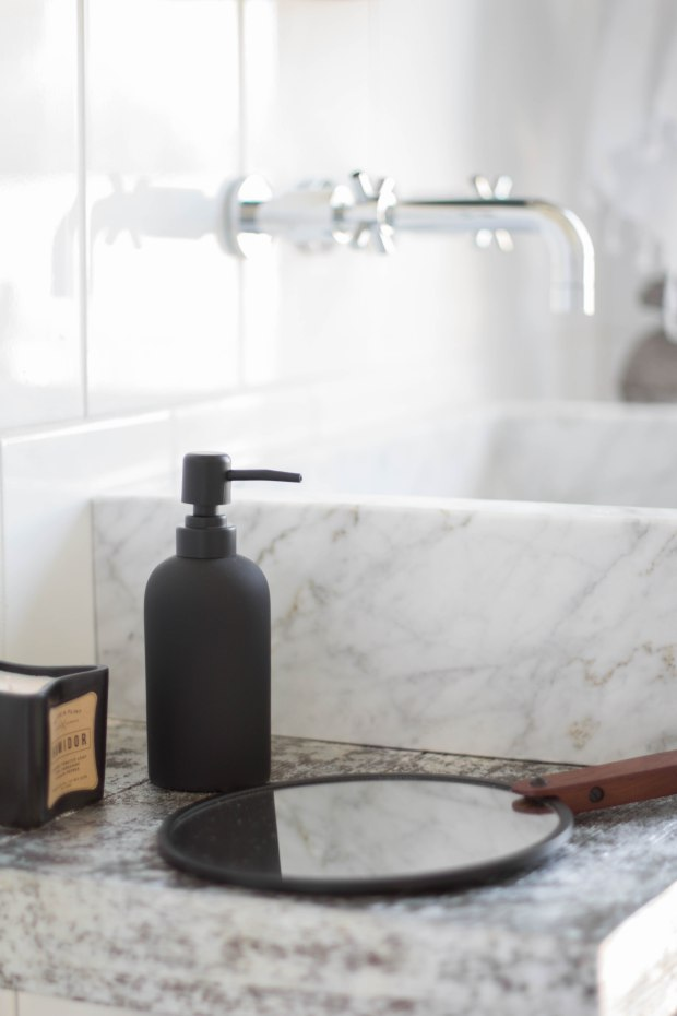 koa-house_pool-bathroom-black-and-white-wall-mount-faucet-marble-blck-sink-hand-mirror